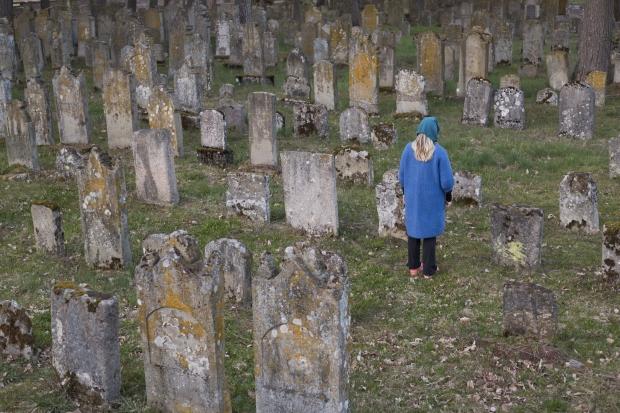 Eine Frau steht auf dem jüdischen Friedhof in Bechhofen und betrachtet einen Grabstein